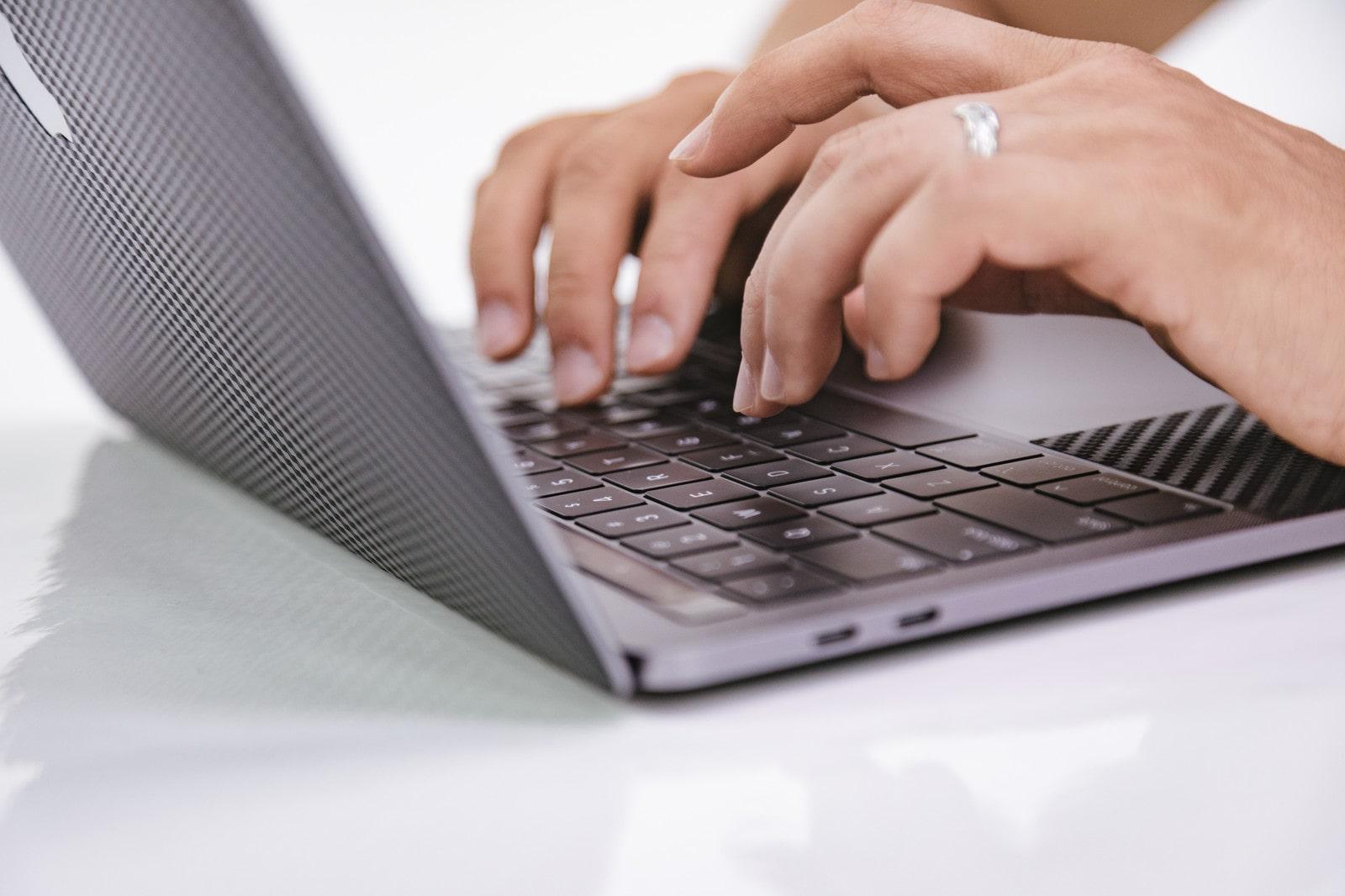 ノートパソコンでタイピングをする男性