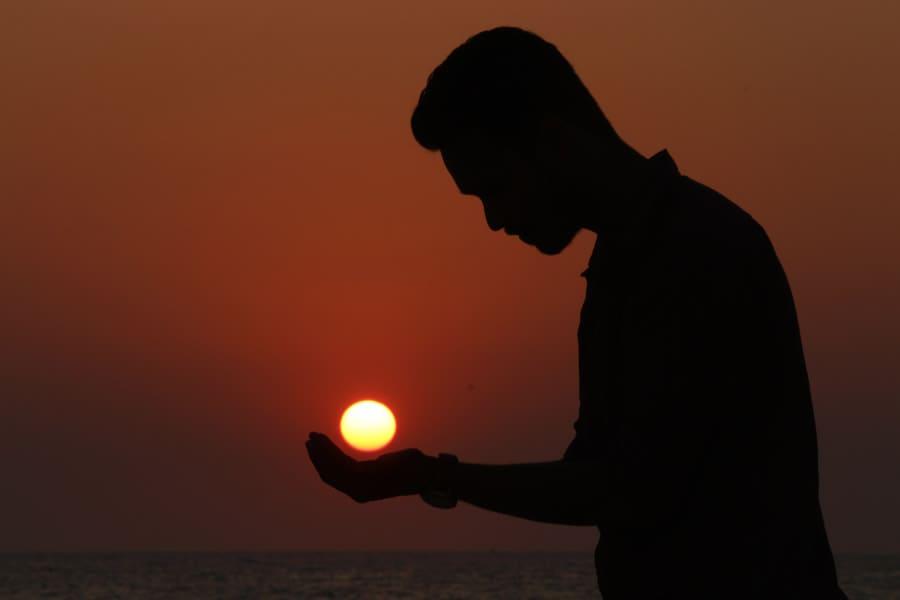 夕日に手をかざす男性