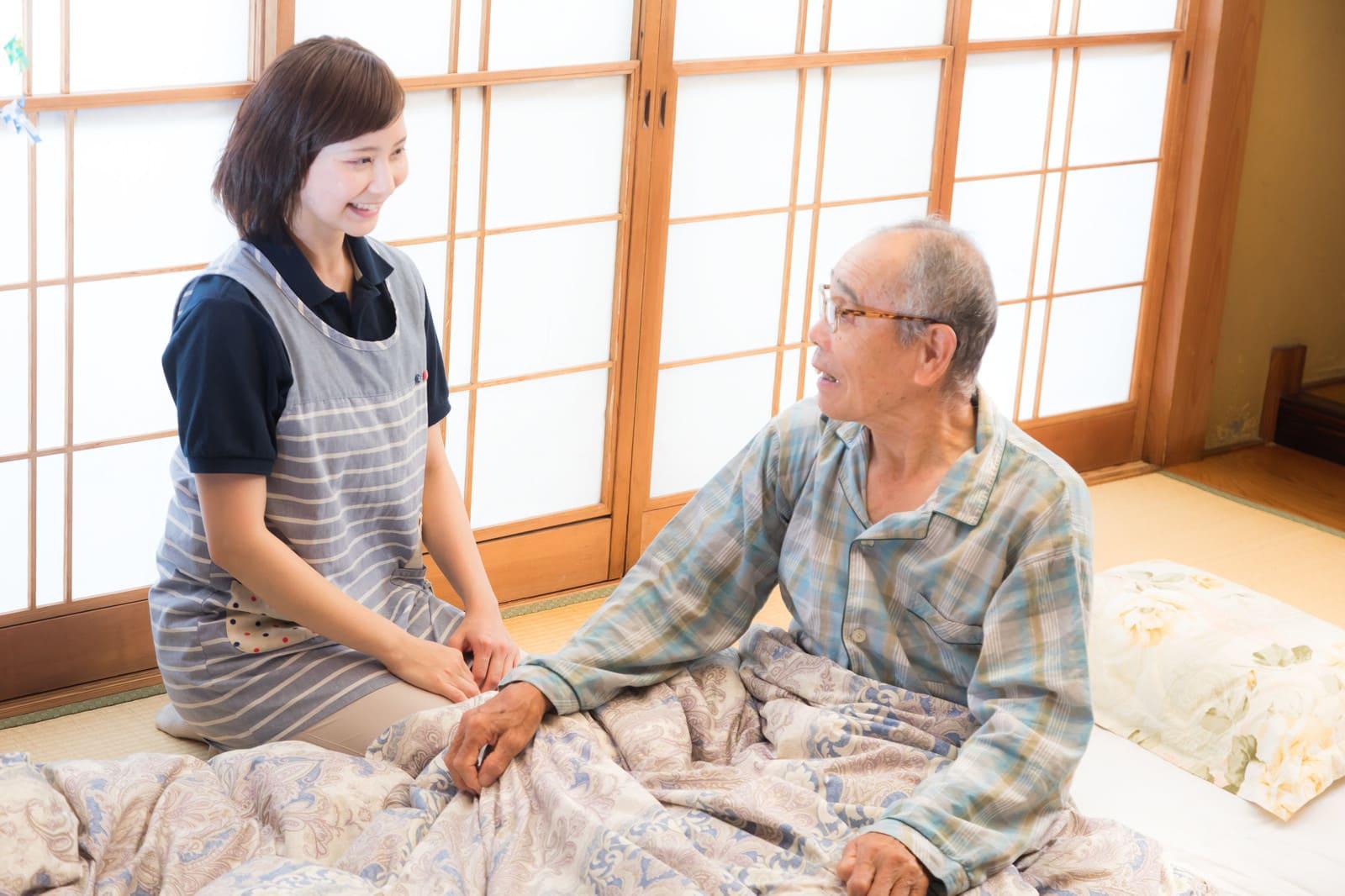 座っている老人と話す女性