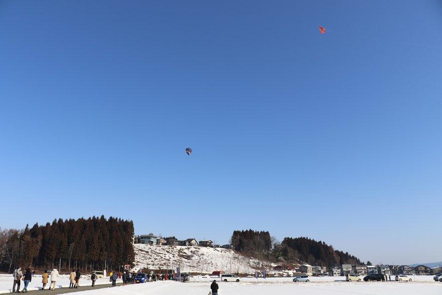 応援の凧と見送られる熱気球